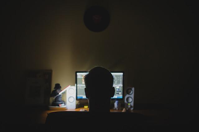 muž ve tmě za počítačem